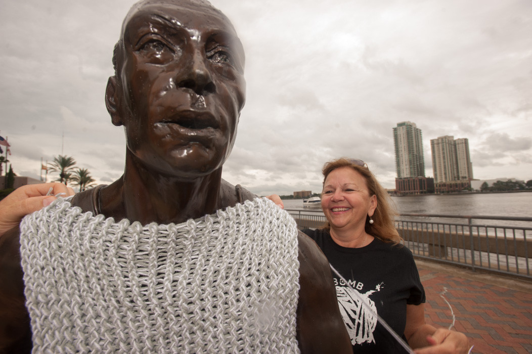 Shannon Palmer puts a smock on the runners statue on the river walk.
