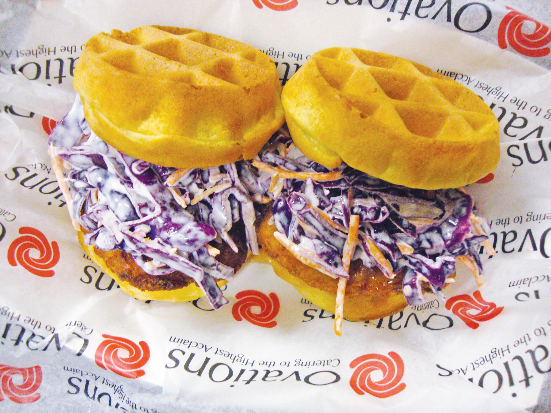 Golden Belgian waffles are topped with a hunk of fried white-meat chicken breast, a sweet-and-spicy red cabbage slaw and touch of tangy Krystal hot sauce and honey.