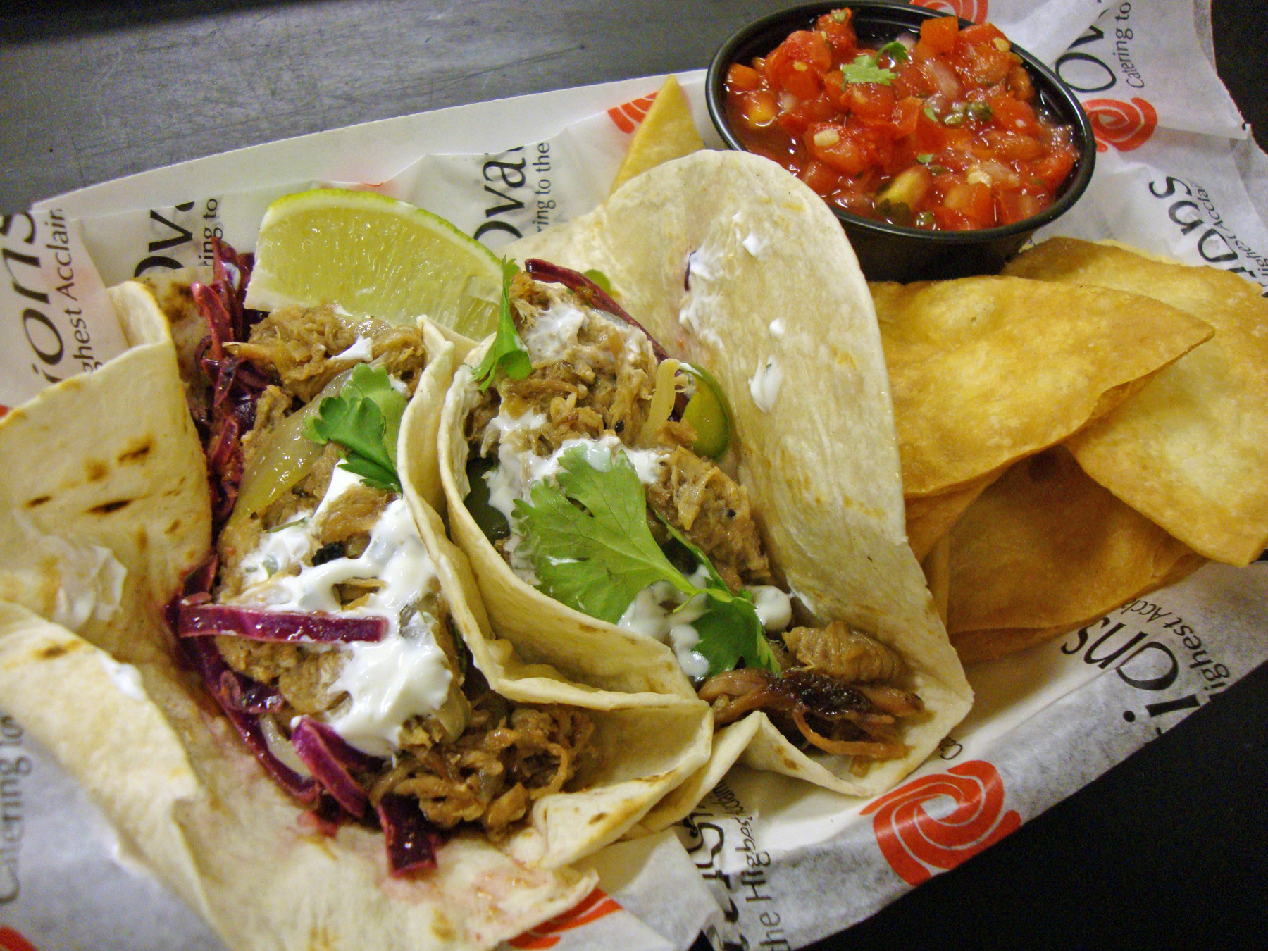 The Duval Taco Company's smoky braised pulled-pork carnitas include a sautéed green-pepper-and-onion medley and cilantro lime crema.