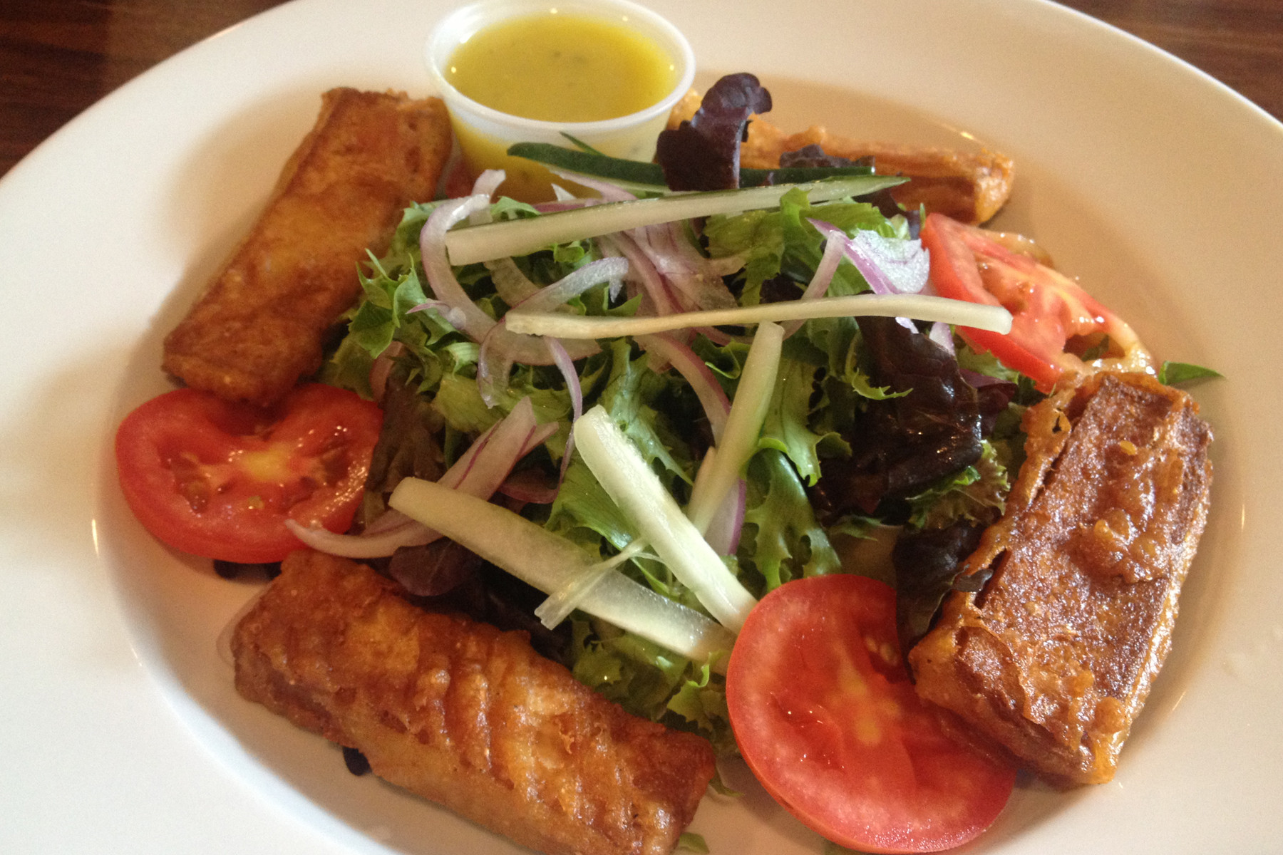 "The house salad can be topped with your choice of a protein, including crisp golden tofu ""fingers."""