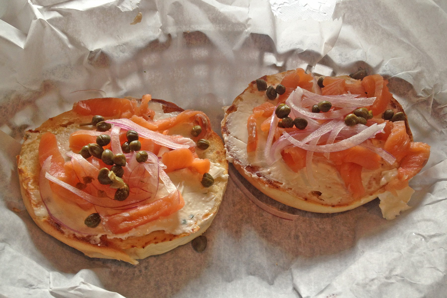 From the sandwich menu, cold-smoked salmon with lemon chive cream cheese, capers and red onion slivers top a crisp toasted bagel.
