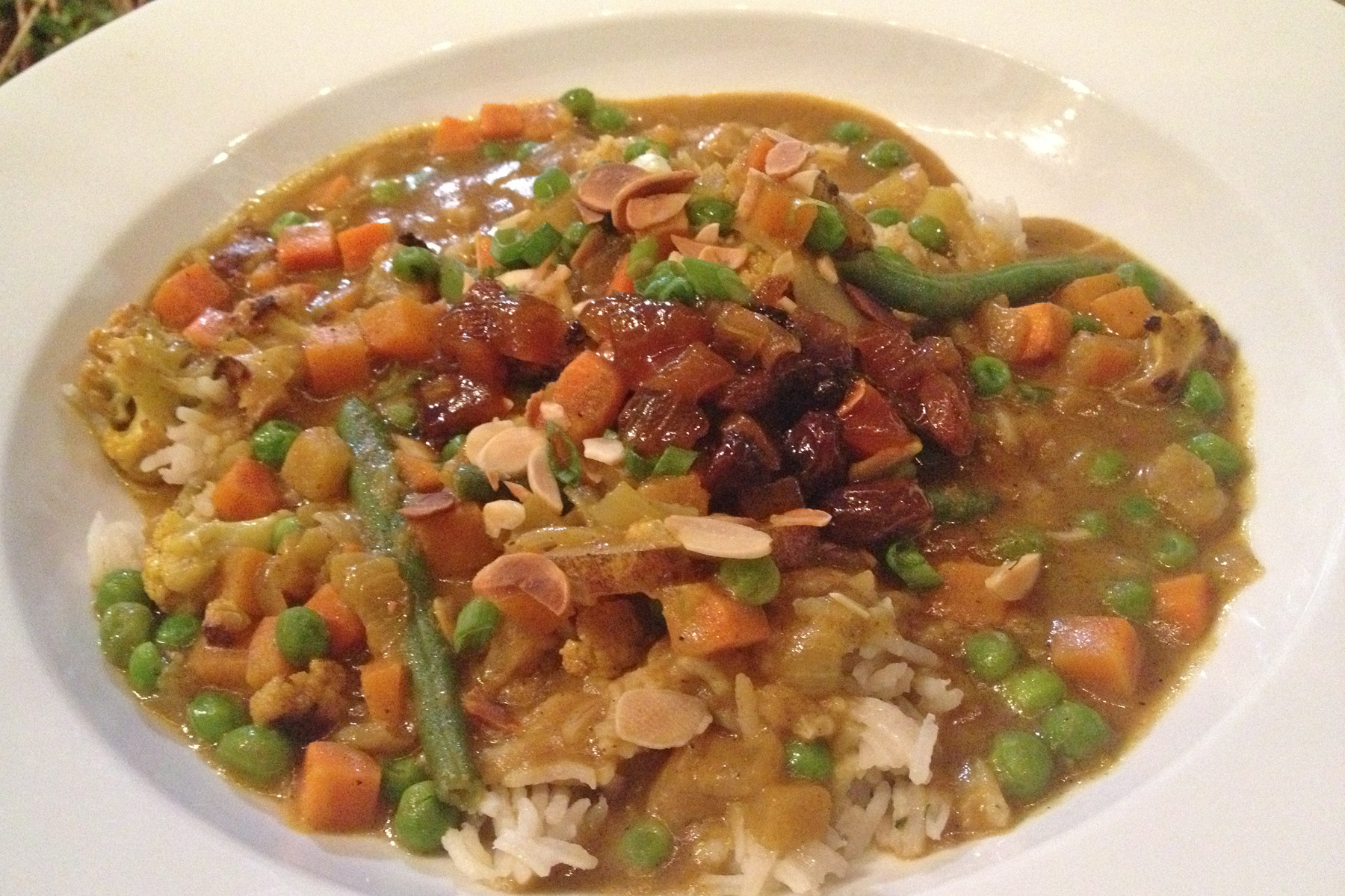 Veggie curry atop basmati rice is available at lunch or dinner and is chock full of carrots, peas and cauliflower.