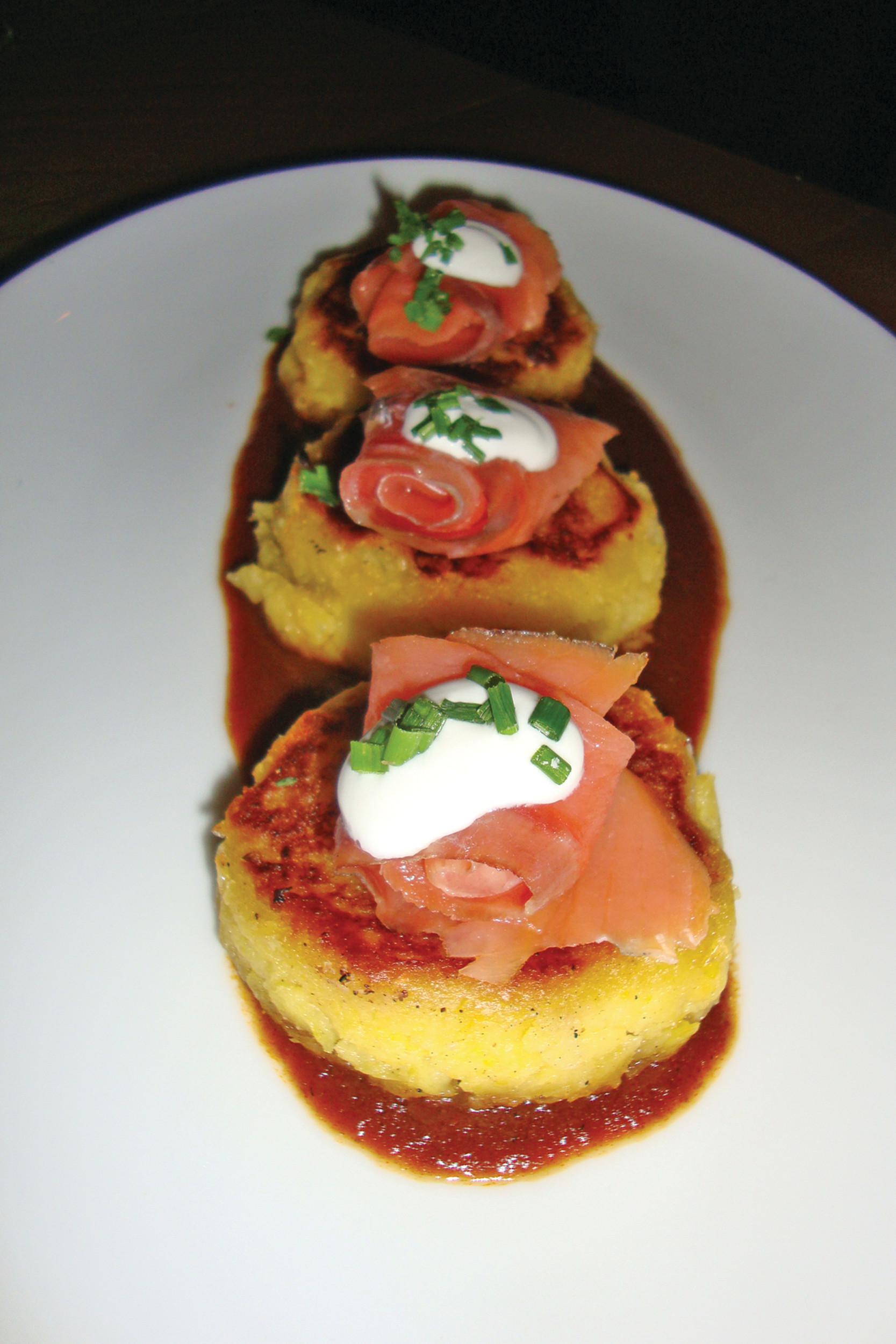 The trio of tamale cakes topped with smoked salmon, house crema and scallions pairs nicely with the accompanying ancho chile sauce.