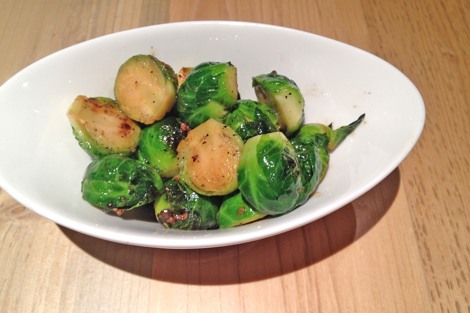 The crisp and vibrant green Brussels spouts are tossed in a warm bacon vinaigrette.