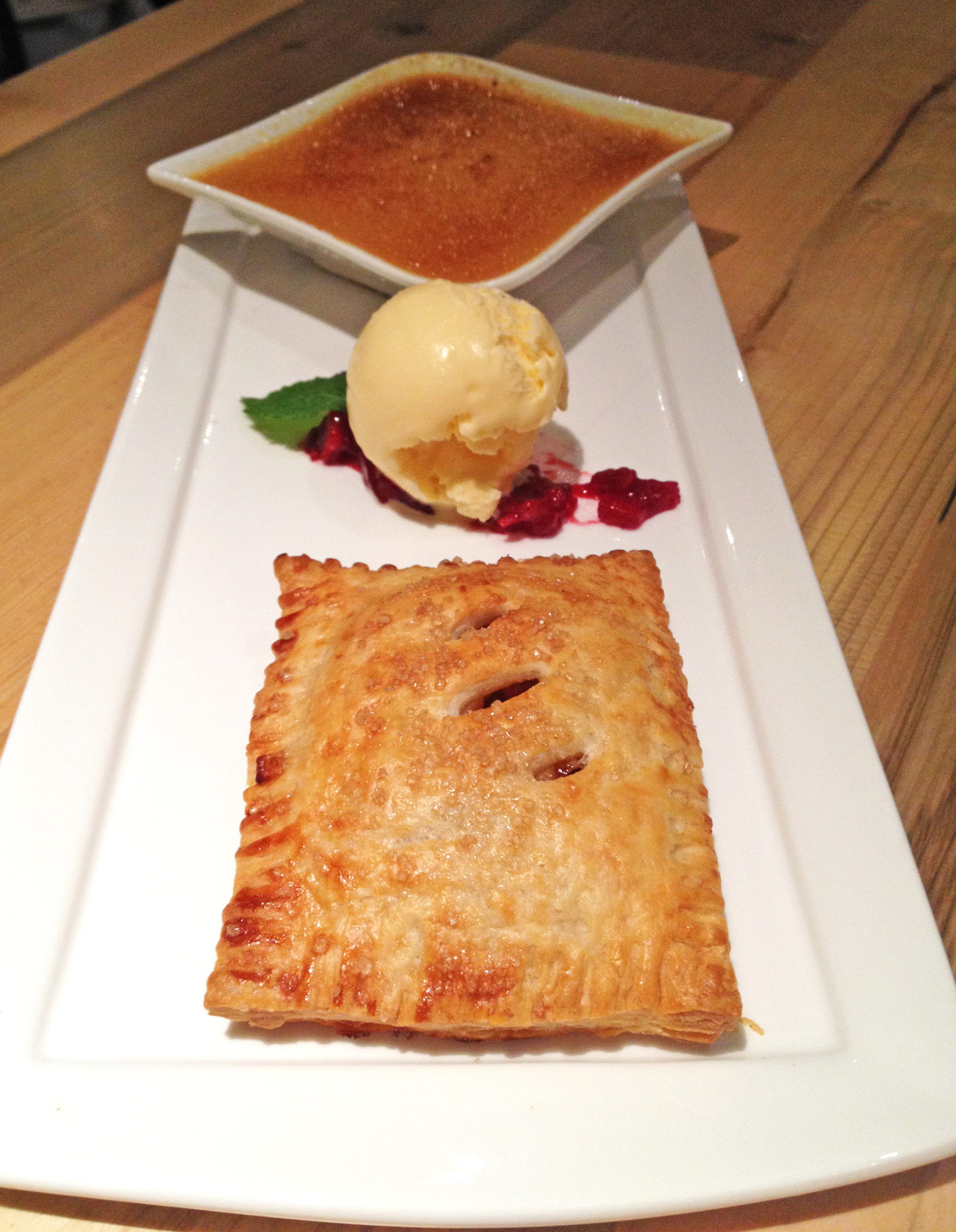 The apple hand pie accompanied by salted custard and a mound of French vanilla ice cream offers a fun twist on traditional apple pie.