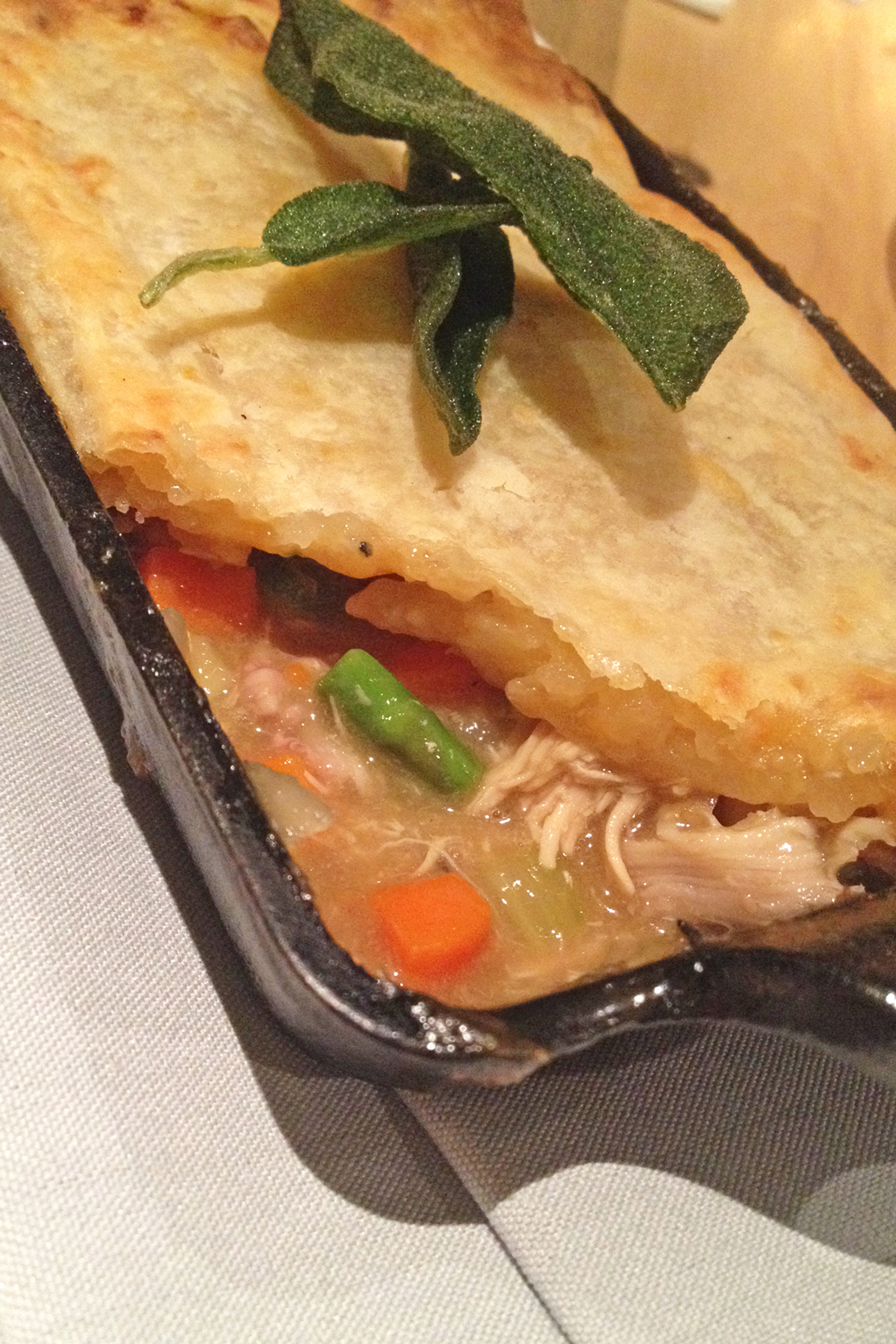 Topped with sage, the cast-iron chicken pot pie is loaded with chicken pieces and hearty vegetables — asparagus, carrots and lima beans.