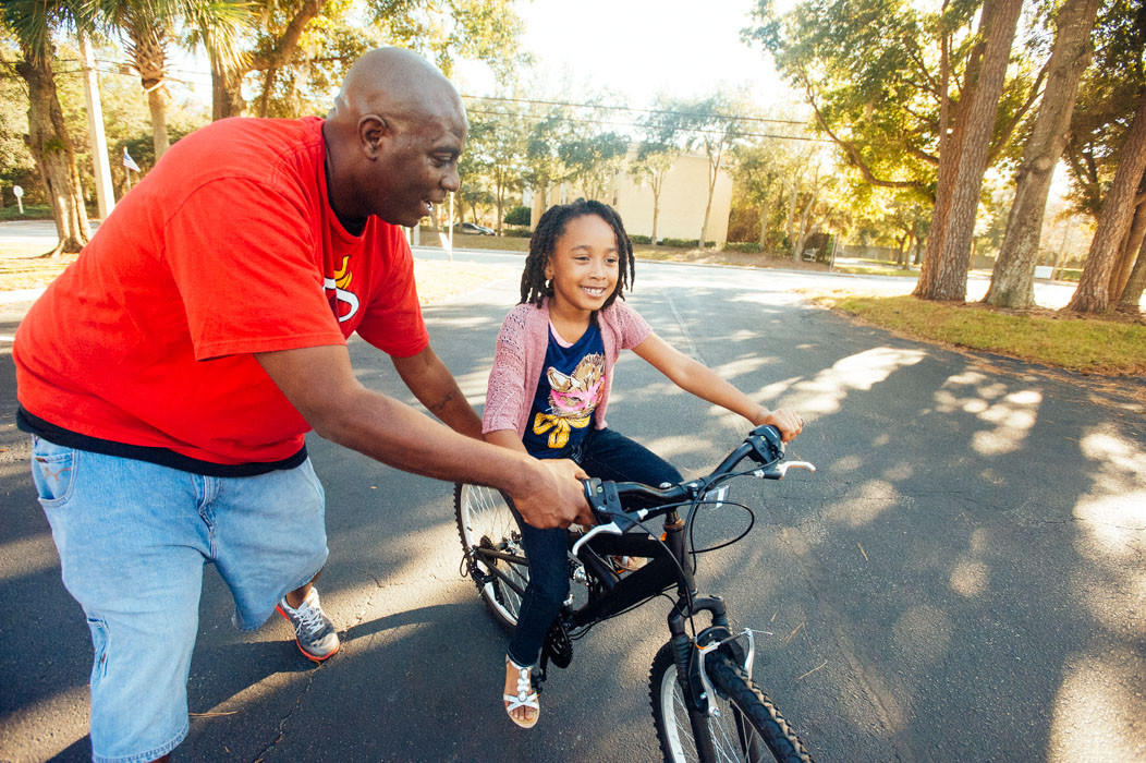 Omotoya Richmond, who launched the original change.org petition to rename Nathan Bedford Forrest High School, helps a neighborhood girl learn to ride a bicycle.