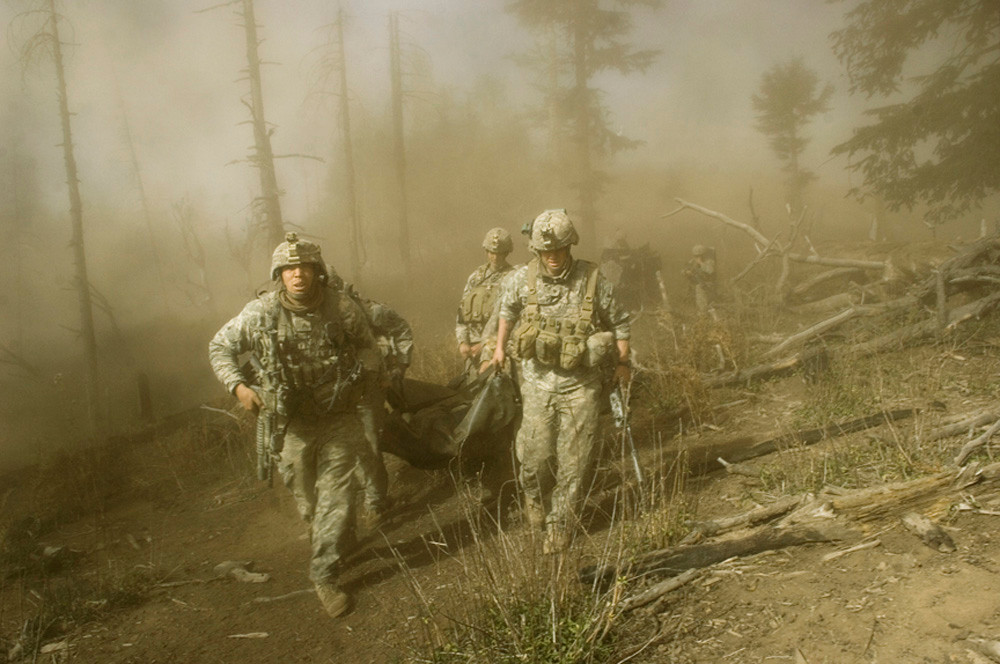 Sgt. John Clinard, left, and Jay Liske, right, and other soldiers from Battle Company, 173rd Division carry the body of Sgt. Larry Rougle of Utah, towards the medevac helicopter along the Abas Ghar ridgeline in the mountains in Korengal Valley, Kunar province, Afghanistan on Oct. 23, 2007. Rougle was killed less than an hour prior while their unit, a scout team, was standing guard at the furthest tip of a ridge, and was ambushed by the Taliban. Two other soldiers, Sgt. Kevin Rice and Spc. Carl Vandeberge were shot and wounded, and were medevaced out for surgery minutes before. The soldiers were on a battalian-wide mission to look for caves and weapons caches and known anti-coalition leaders
