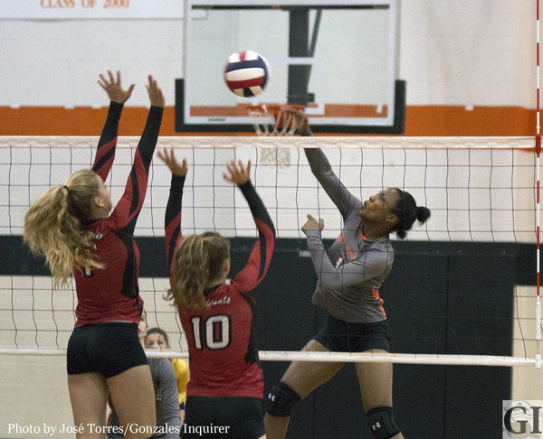 Chelsie Hastings goes up for a swing as Grace Irvin (1) and Riley Johnson (10) attempt a block in Shiner St. Paul's three-set win over Gonzales.