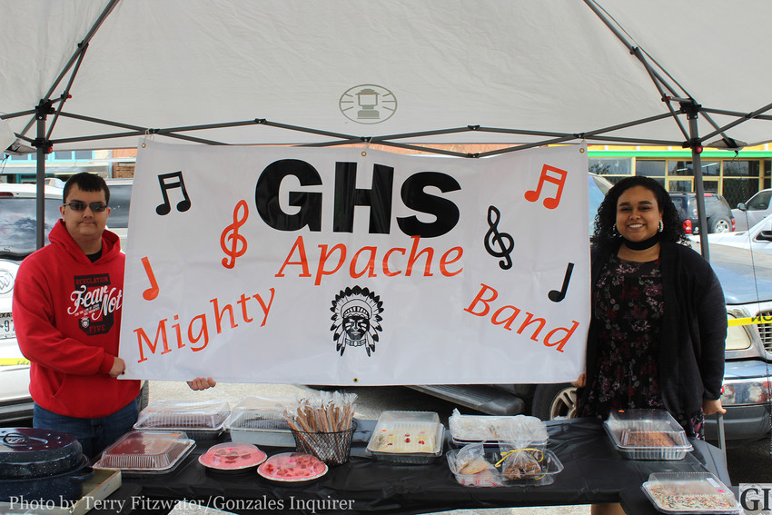 Joshua Kenning, left, a sophomore baritone player at Gonzales High holds the sign in the booth where band boosters were trying to raise money for new band uniforms by selling cakes, pies, pudding and other sweets. Also pictured is freshman Color Guard member Aaliyah Castro.