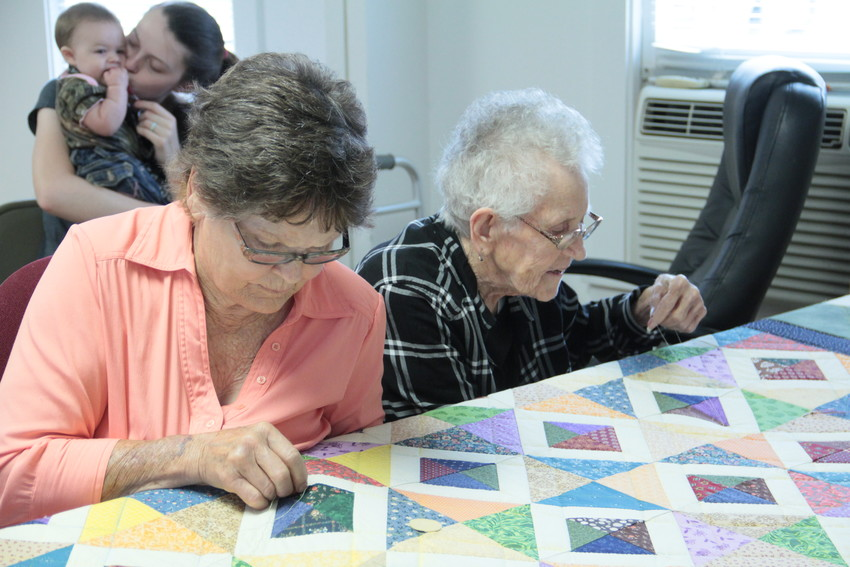 Margie Rice, left, and Janyce Littlefield, right, work on the quilt for the Leesville Country Fair auction. The work is the big-ticket item, fetching upwards of $2,000. Newest quilter-in-training Brooklyn looks on in interest from the back.