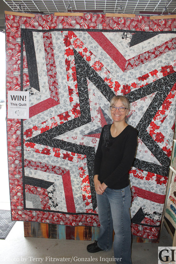 Denise Green poses in front of a quilt that will be raffled off to help support Luling PD's Blue Santa promotion this holiday season.