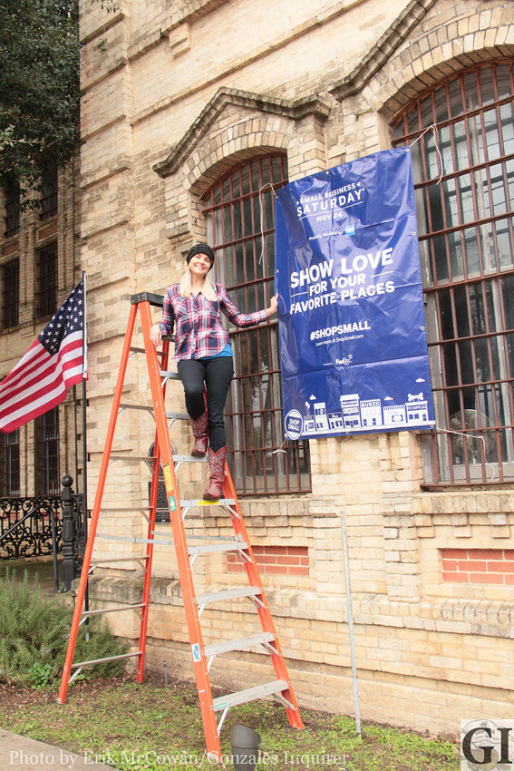 Gonzales Chamber of Commerce Executive Director Daisy Scheske Freeman wants to let the town know that Small Business Saturday is coming up next week. Here, she hangs a banner off of her offices at the Old Jail.