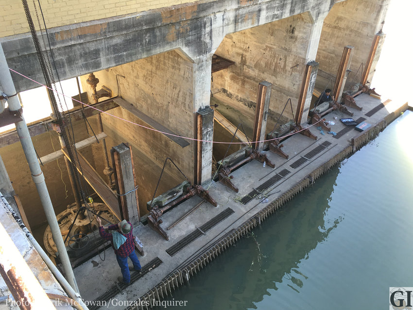 The three units at the Gonzales hydroelectric dam sit idle awaiting repairs as workers amble around preparing them for removal and rehabilitation.