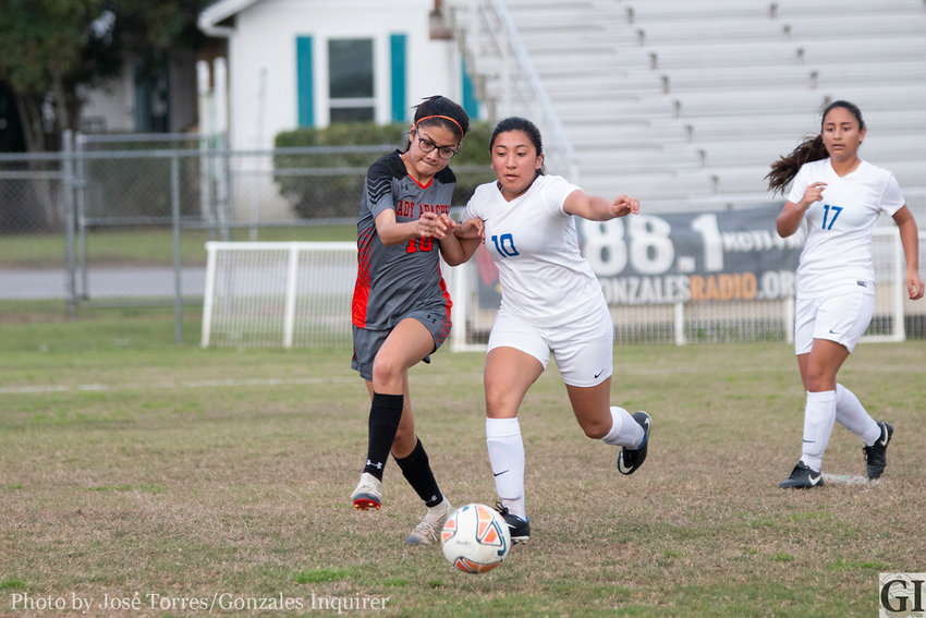 Natalya Cruz (10, left) fights through a defender for possession in Gonzales' 2-0 victory last Friday. The Lady Apaches moved to third place after their Senior Night win.