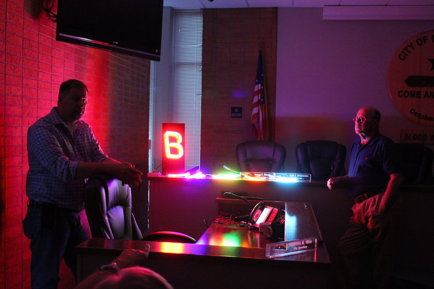 Allen Sawyer (left), National Signs representative, demonstrates two LED options to be used for the Lynn Theater sign and marquee to Tommy Cox (right) and the rest of the present GEDC board.