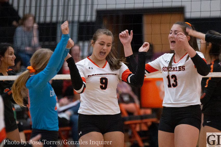 Kristin Baker (9) and Hayley Sample (13) celebrate a kill with the team.