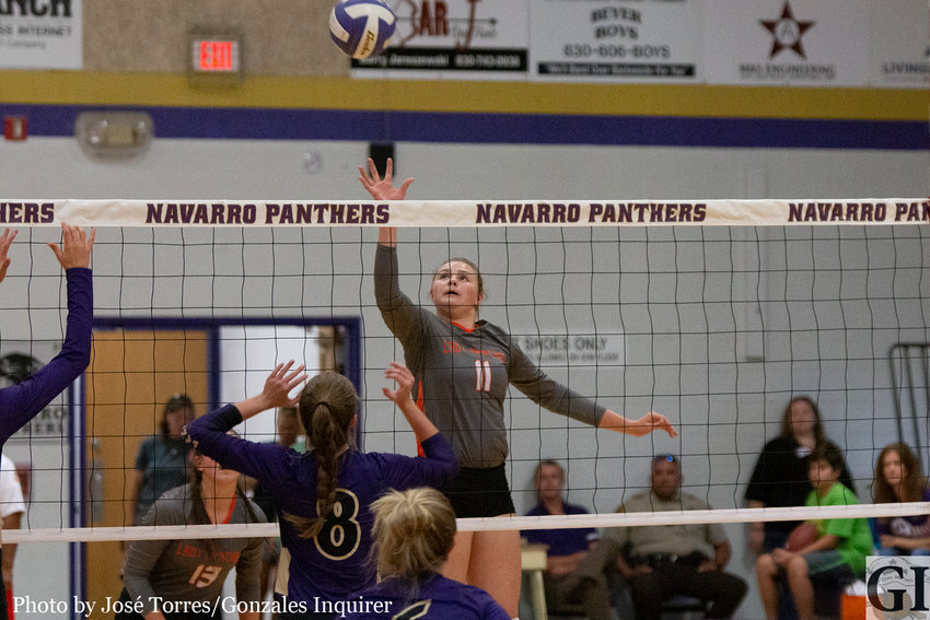 Madelynn Brown (11) comes away with a kill in Gonzales' four-set loss to Navarro.