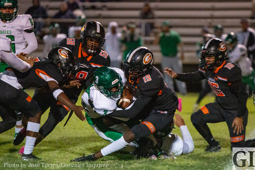 A group of Apache defenders surround Pleasanton in Gonzales' 20-13 district victory on Friday.