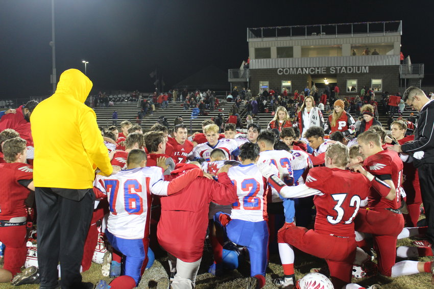 Players from both Shiner St. Paul and San Antonio St. Gerard kneel for prayer after Friday's game at Comanche Stadium. The Cardinals came away with a 42-14 win.