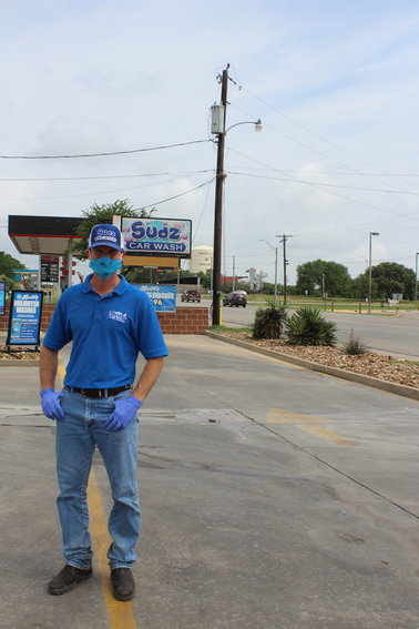 Standing in front of his sign is Craig Golham, owner of Sudz Car Wash, who took on the task of supplying Gonzales hospital workers with free cleanings as his way of giving back to the healthcare community.