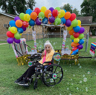 "Maria De Jesus ""Jesusa"" Almaraz poses in front of one of the parade floats Monday in honor of her 103rd birthday."