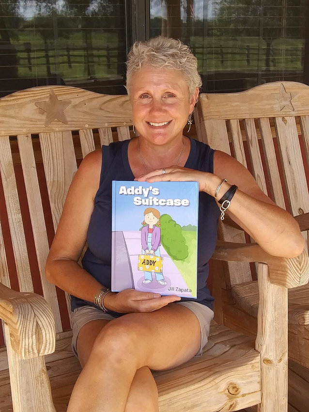 """Jill Zapata holds a copy of """"Addy's Suitcase,"""" her first children's book which was just recently published."""