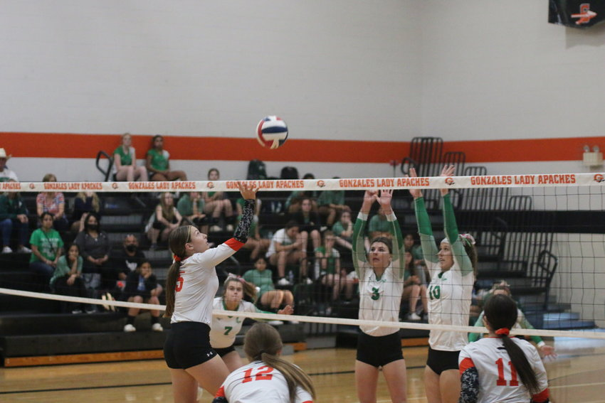 Sydney McCray (5) tries to catch Pleasanton off balance with a dink while Macy Sample (12) and Tara Lester (11) look on.