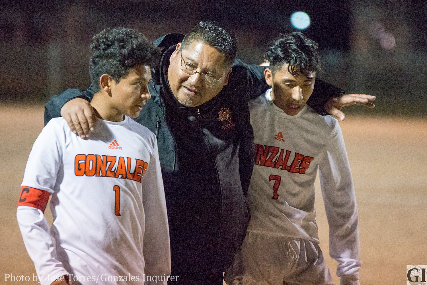 Head Coach Greg Ramirez advises players Anthony Veliz (1) and Luis Lejia (7) during the half.