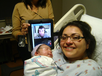 Utilizing the Skype® computer software application for an Internet video call from a U.S. military base in Afghanistan to Texas, Sgt. Joshua Sanchez was able to witness the birth of his first child last week. Mom Monica Leal and baby Bradyn were joined by Dad via an iPad (held, at left, by Joshua's mother, Aida Rodriguez).