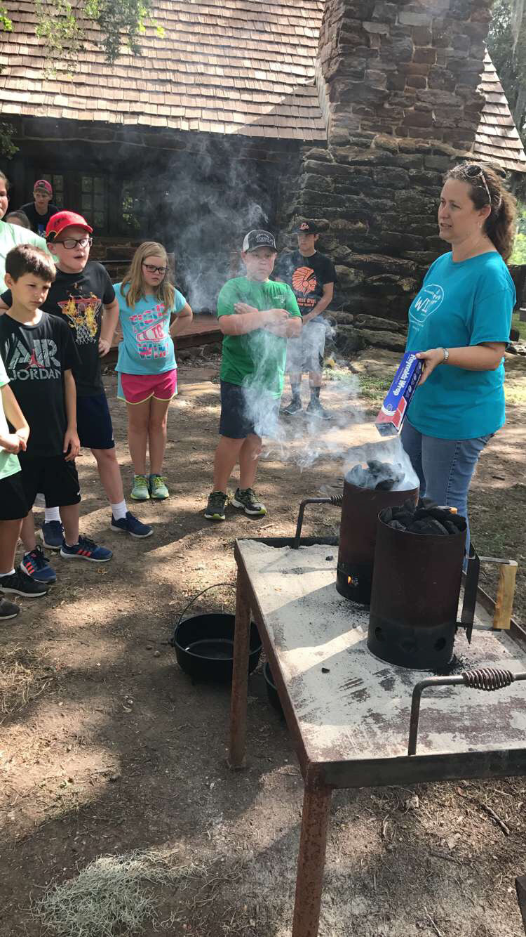 A volunteer helps out in a camp cooking demonstration at a past Friends of Palmetto summer camp.