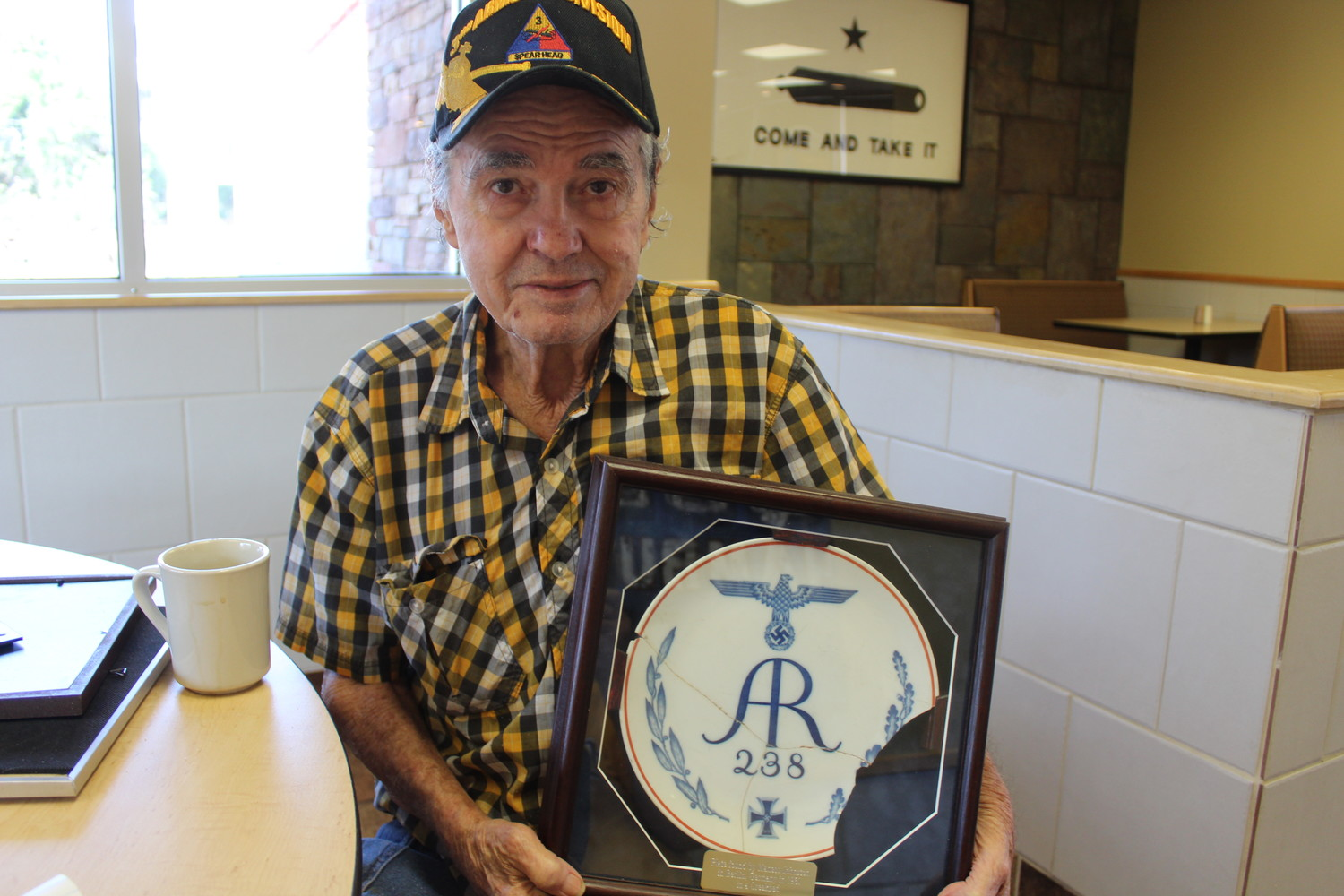 Maness Johnston holds the Nazi Luftwaffe plate he discovered in a dry creek bed in West Berlin.