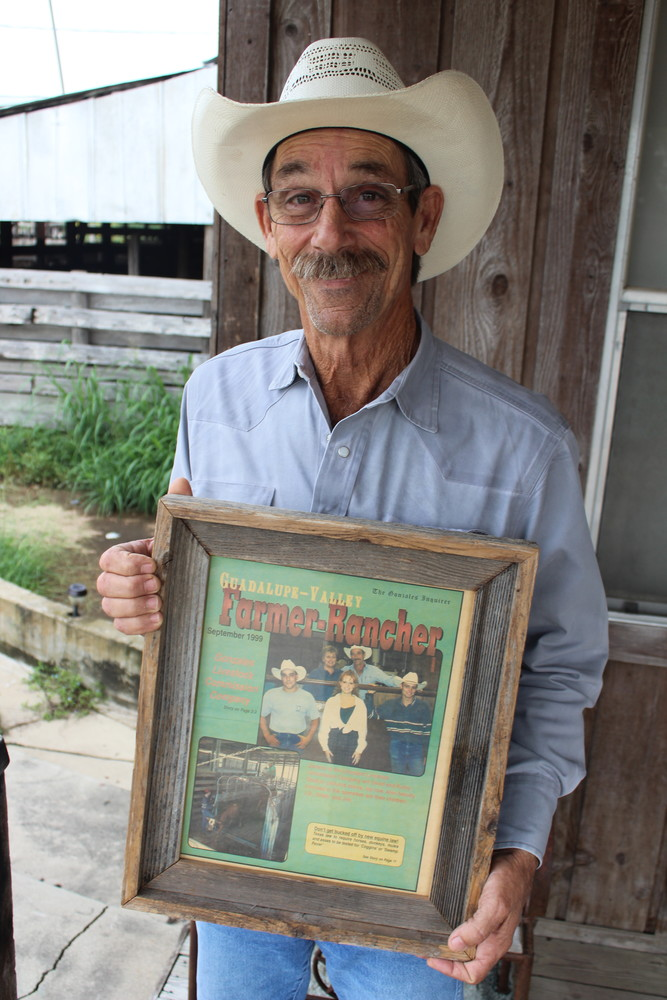 David Shelton holds a picture of the story the Gonzales Inquirer put together announcing his purchase of the Gonzales Livestock Auction House in July, 1999.