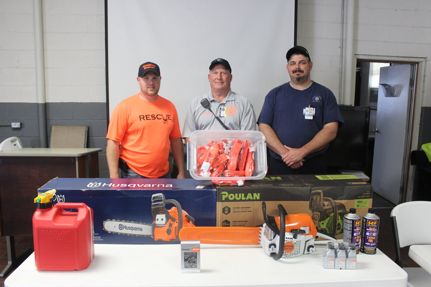 Tony Matias, Ken Colwell and James Cole of Gonzales County Rescue stand behind the new chain saws and tourniquets that were donated by area businesses to help support Rescue.