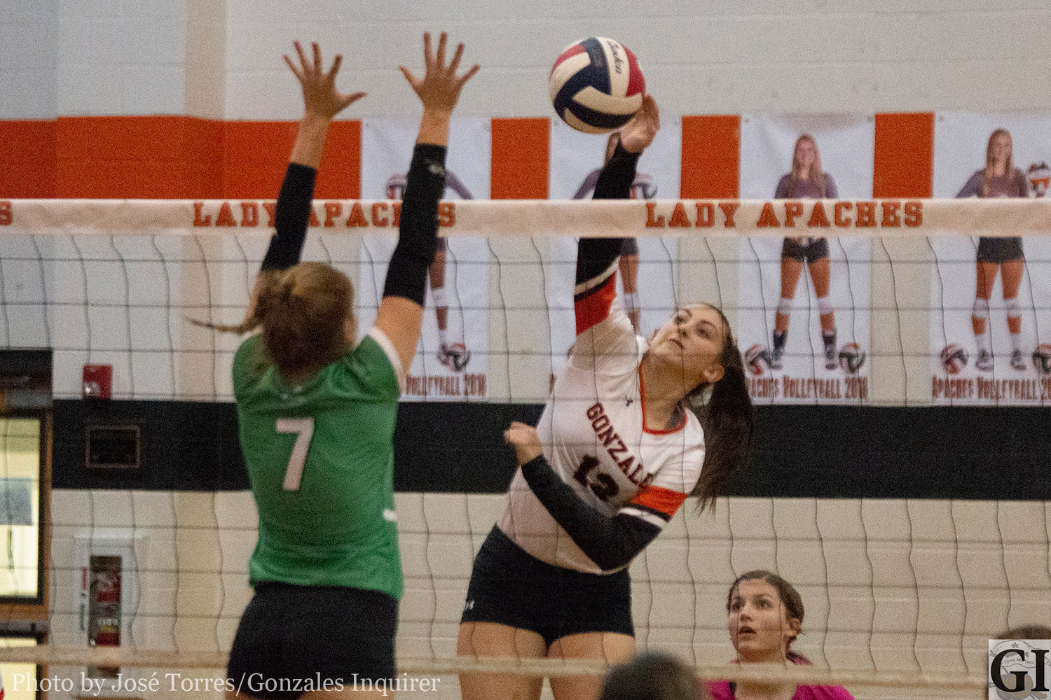 Hayley Sample (13) goes up for a swing in Gonzales' three-set loss to Cuero on Tuesday.
