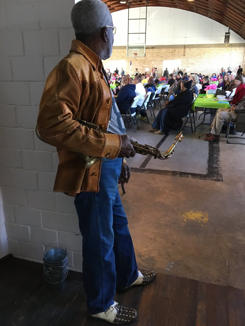 Local saxophonist and community elder O.S. Grant waits for his turn to serenade the crowd at the Edwards Community Center.