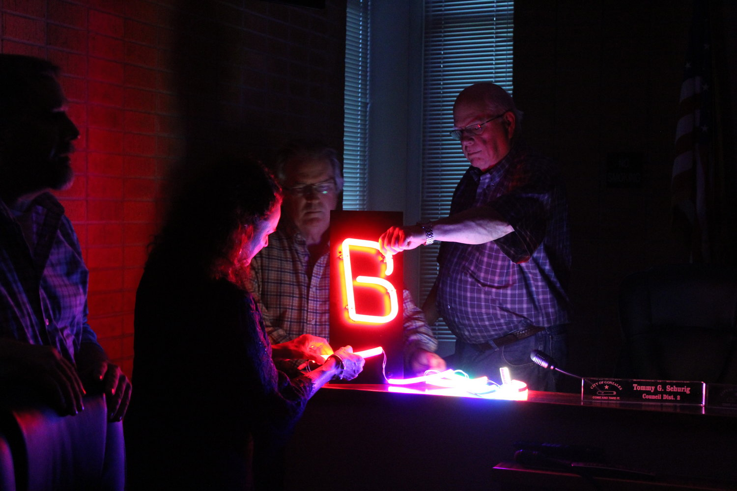 Board Member Dan Blakemore (right) feels the firm LED display as GEDC President/CEO Genora Young (second to left) and Board Member Steve Sucher (center) investigate the malleable string lights. Allen Sawyer (far left), National Signs representative, brought two LED displays for the GEDC to compare. Ultimately, GEDC went with the string lights.