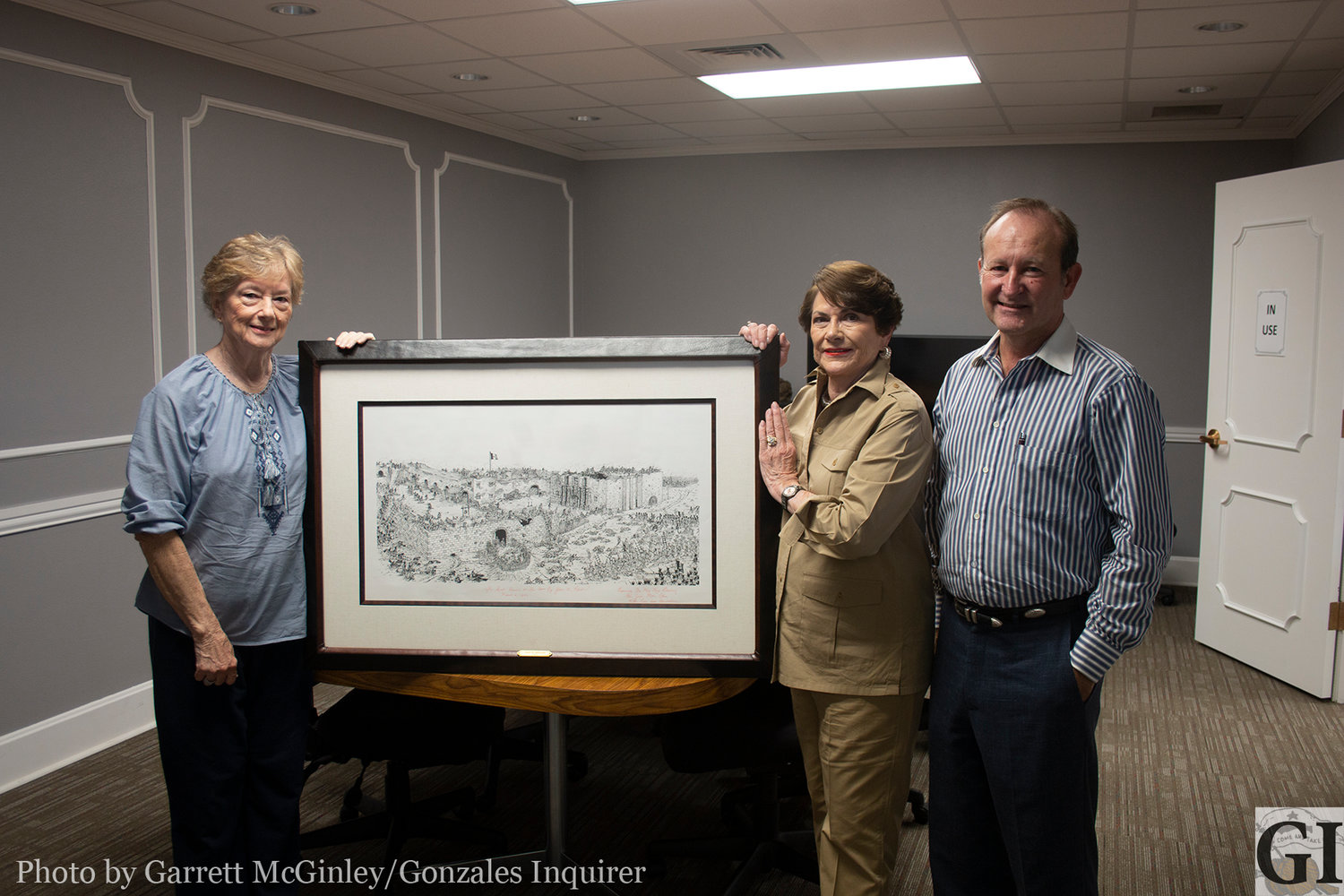 Clint Hille, Carol Eakman and Library Board President Vicki Frenzel pose with the James Robertson drawing donated by Rex Bushong on behalf of his late wife Vickie.