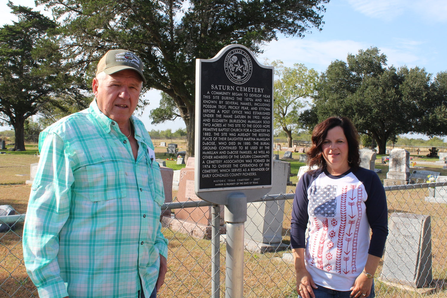 Joe Solansky (left) and Melissa Clampit stand in front of the Saturn Cemetery Historic Register marker while work is being done to clean up and restore the grave sites of 93 veterans interred in the ceremony.