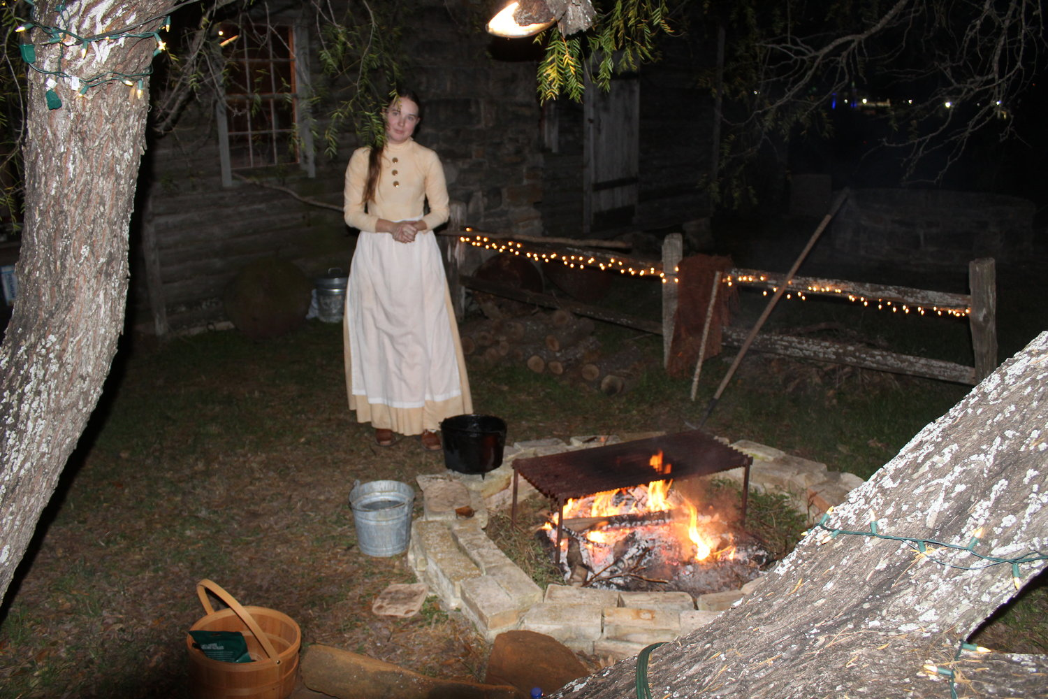 A costumed interpreter stokes the fire before visitors approached her building on Friday night.