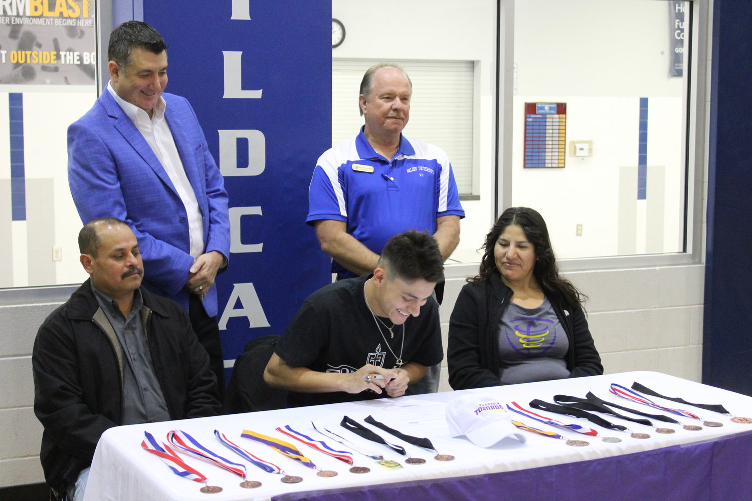 Miguel Morales, surrounded by parents and Waelder ISD administrators, signs his letter of intent to run for Concordia University Texas.