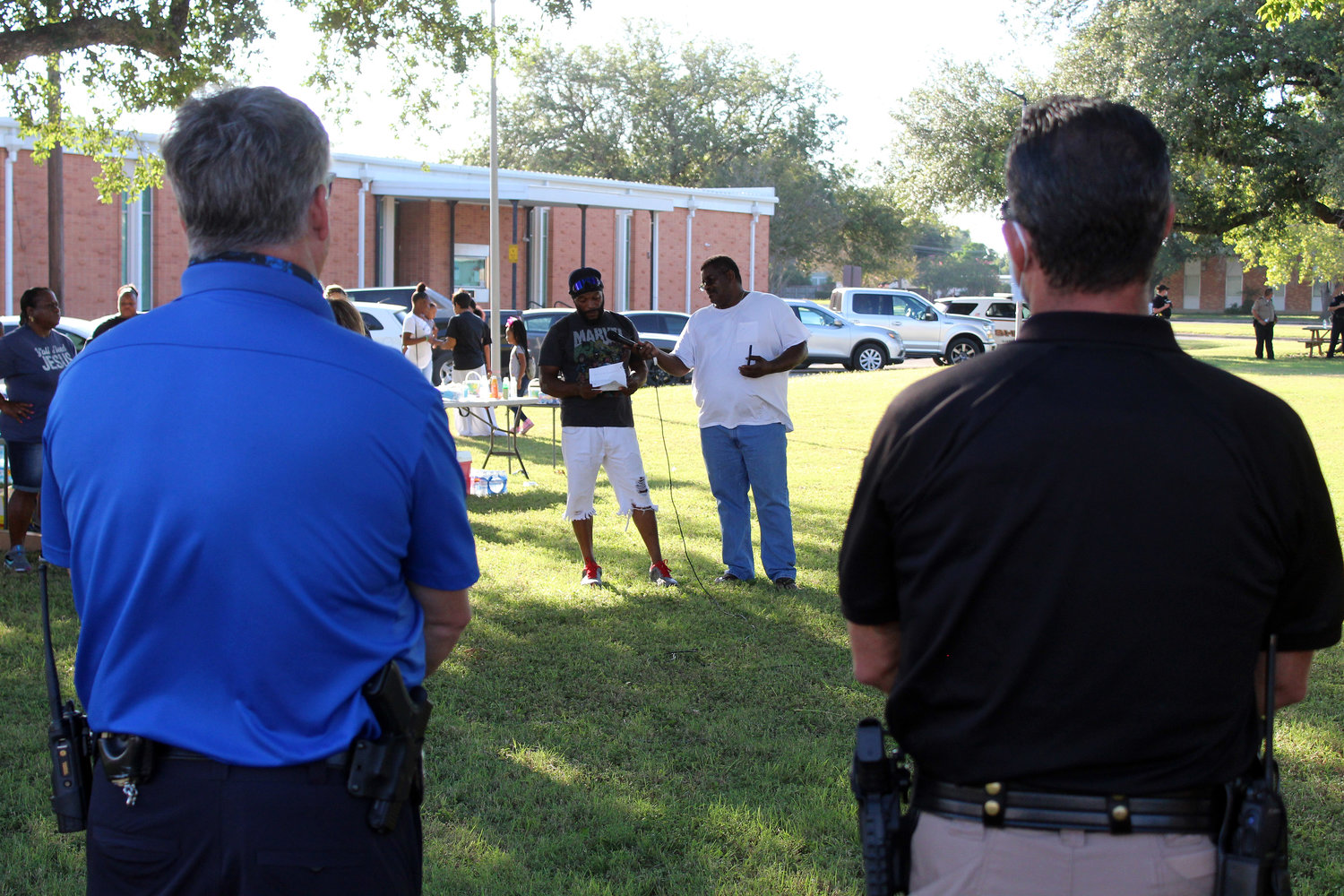 Gonzales Police Chief Tim Crow, left, and Gonzales County Sheriff Matthew Atkinson, right, listen to speakers at Friday's Juneteenth celebration at City Hall.