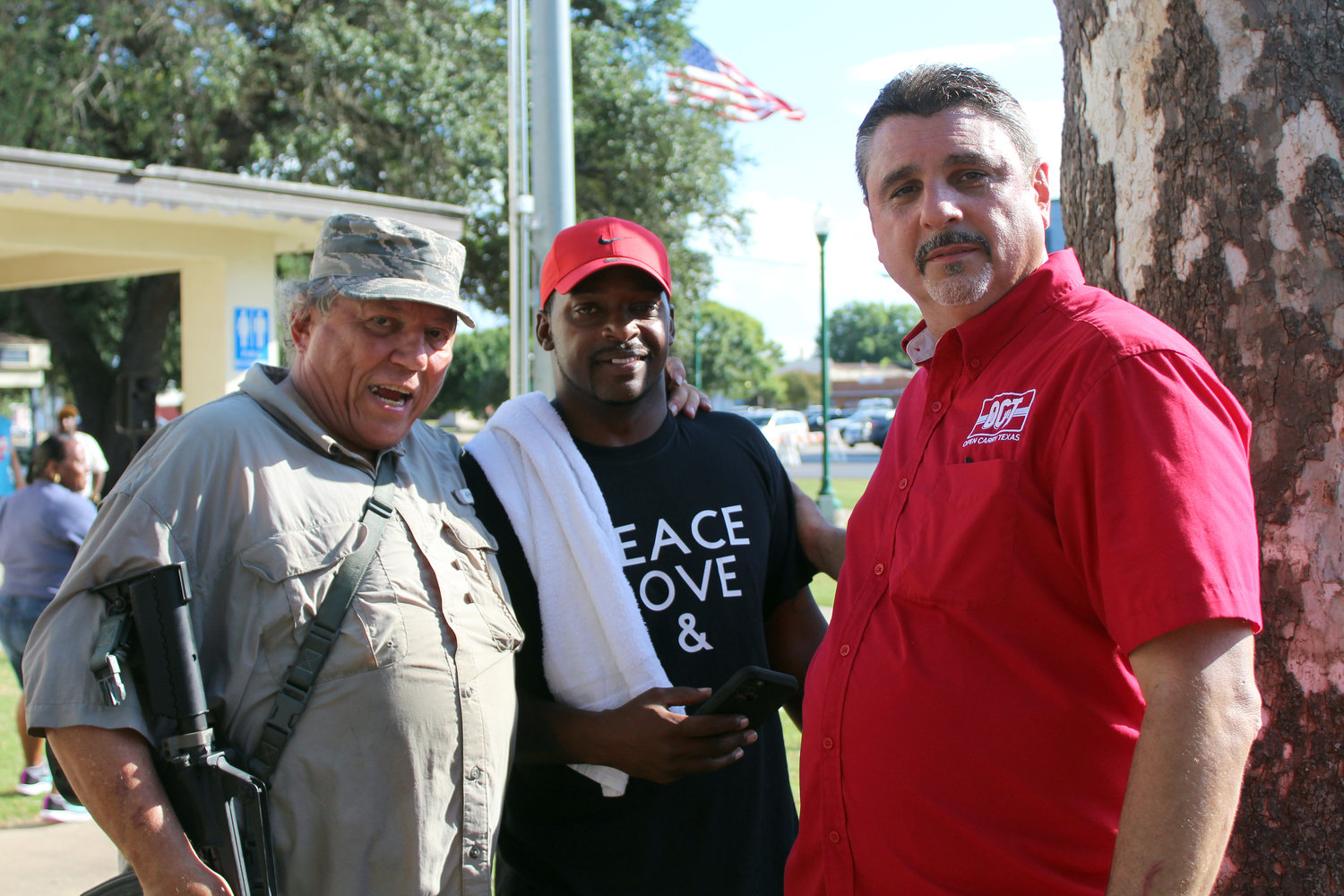 Mark Gurgevich, left, and David Amad, right, representing This is Texas Freedom Force and Open Cary Texas, meet with Gonzales Juneteenth co-coordinator Joe White prior to the start of the Juneteenth celebration in Confederate Square.