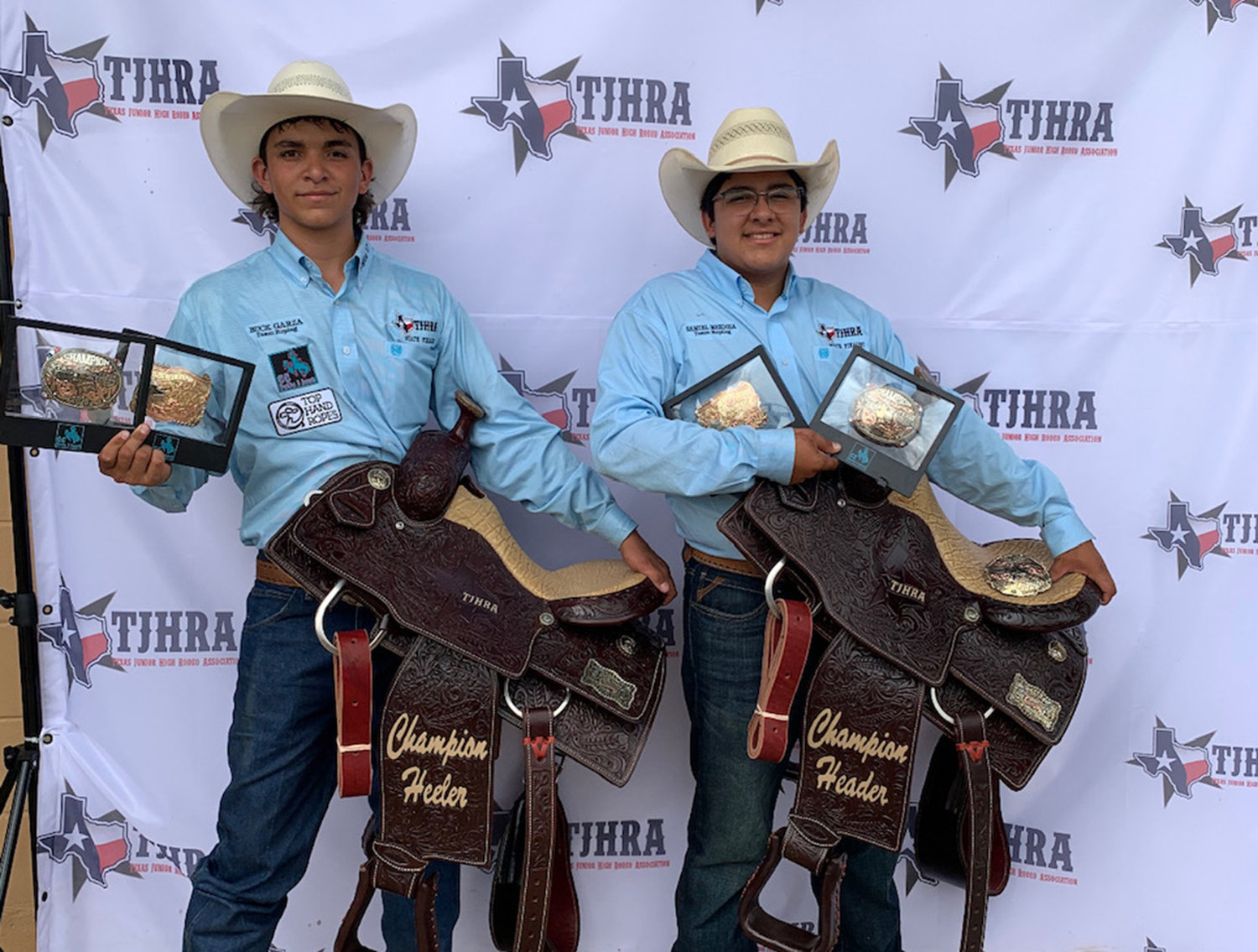 Team ropers Buck Garza (left) and his teammate Samuel Mendoza of Carrizo Springs proudly celebrate their victory at the TJHRA finals last Friday.