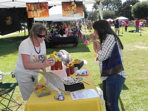 Theresa Callaway, left, representing her daughter Rebekah Hargraves' business B's Bees of Loxley provides a sample for a festival goer at Saturday's Honeybee Festival.