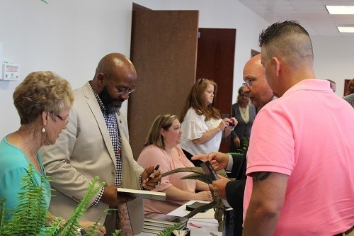 """Baldwin County Sheriff Huey """"Hoss"""" Mack Jr. gets a book signed by the Rev. Chette Williams Sr. at the Central Baldwin Chamber of Commerce's 13th annual Prayer Breakfast at the Baldwin EMC Training Center in Summerdale."""