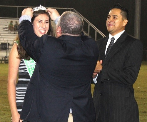 Snook Christian Academy Head of School Thad Butts crowns the school's first-ever Homecoming Queen Alexa Lopez as father Jonathan Lopez looks on.