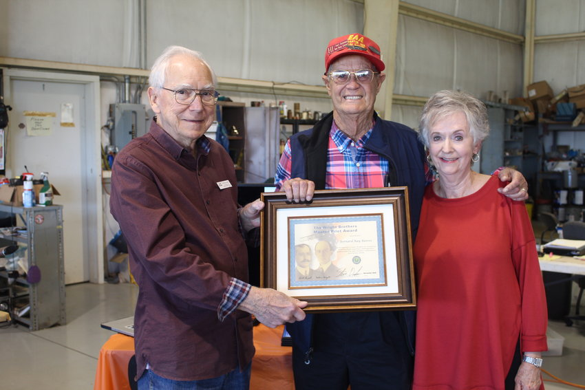 Ray Reeves, pictured with his wife Rita, receives the Wright Brothers Master Pilot Award from Russ Kilgore, president of the Experimental Aircraft Association Chapter 1265 in Magnolia Springs.