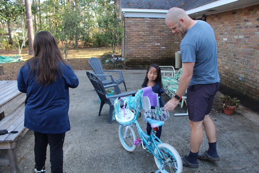 Five-year-old Puja Nelson enjoys riding her bicycle near her home in Bay Minette. Family friend Lisa Miller, a specialist in prosthetics, presented the bicycle to Puja on Thanksgiving. It is fitted with a harness which allows Puja, who was born without arms, to steer with her body.