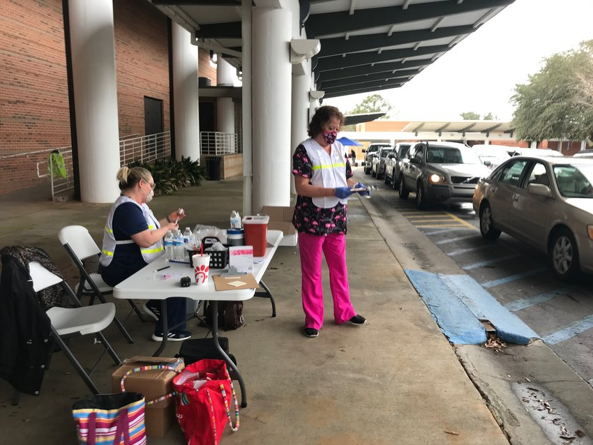 Cars roll through a vaccination clinic in Daphne.